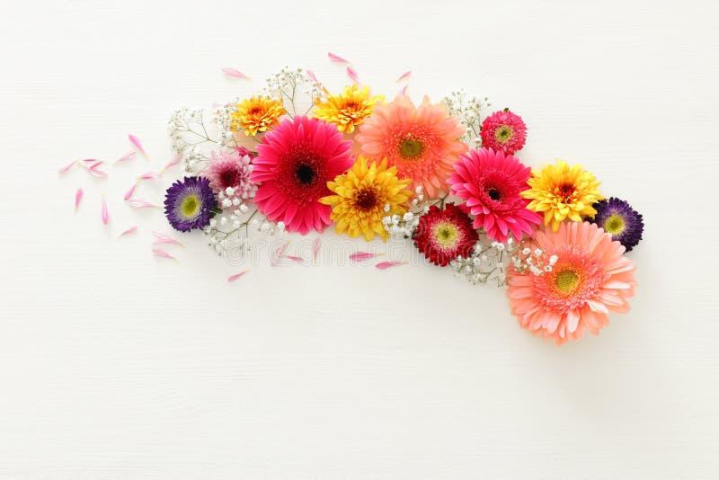 De lenteboeket van roze, gele, oranje en purpere bloemen over witte houten achtergrond De hoogste vlakke mening, legt royalty-vrije stock afbeelding