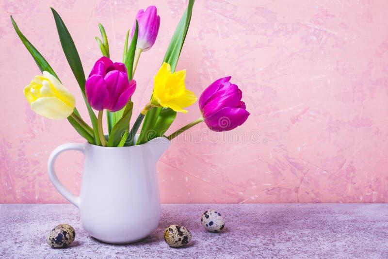 De lenteboeket van tulpen en gele narcissen in een witte vaas De groetkaart van Pasen stock fotografie