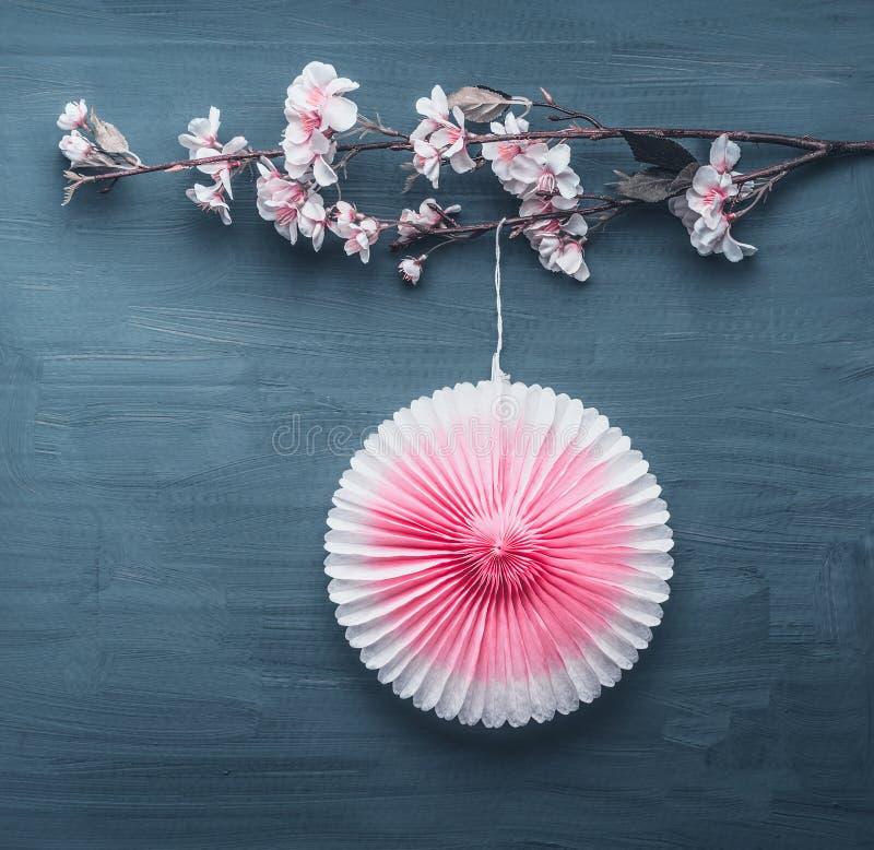 De lentedecoratie met het kunstmatige takje van de de lentebloesem en roze partijdocument ventilator stock fotografie