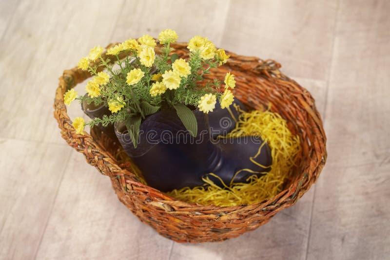 De lentefoto met bloemen in de laarzen van rubberkinderen in een mand royalty-vrije stock foto's