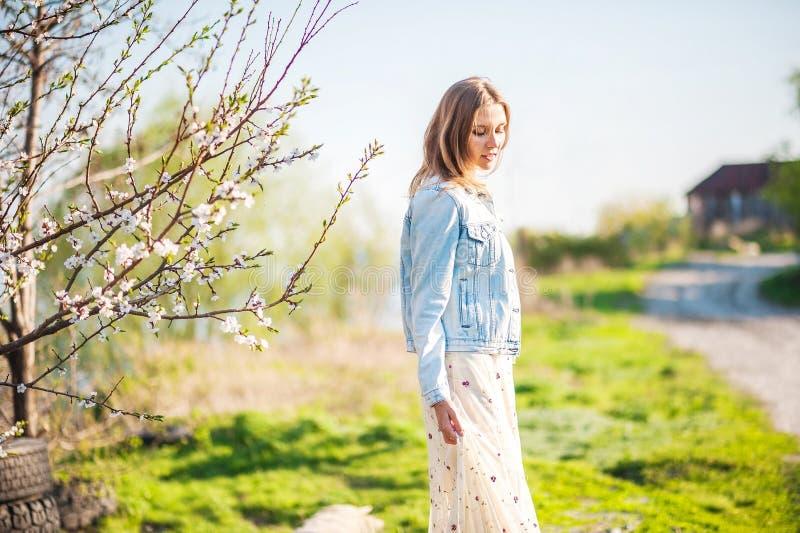 De lentefoto van een mooie jonge vrouw op een achtergrond van aard Meisje in een lichte kleding en een denimjasje in de lente met royalty-vrije stock foto