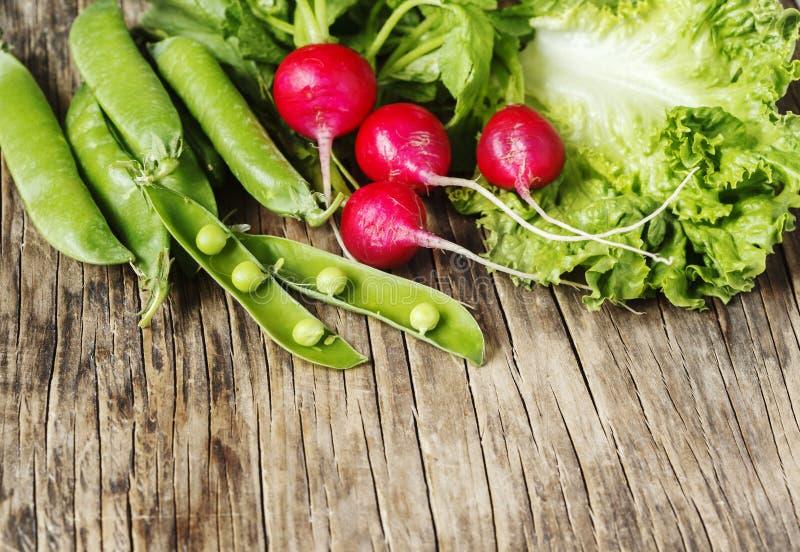 De lentegroenten op houten achtergrond met exemplaarruimte Radijs, groene erwten en groene salade stock afbeeldingen
