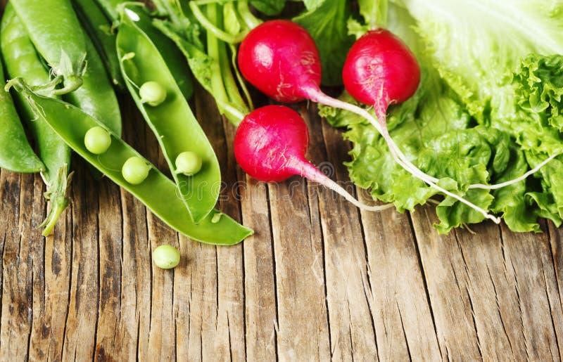 De lentegroenten op houten achtergrond Radijs, groene erwten en groene salade - verse oogst van de tuin stock foto's