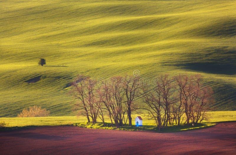 De lentelandschap met verbazende kapel op groene gebieden bij zonsondergang royalty-vrije stock fotografie