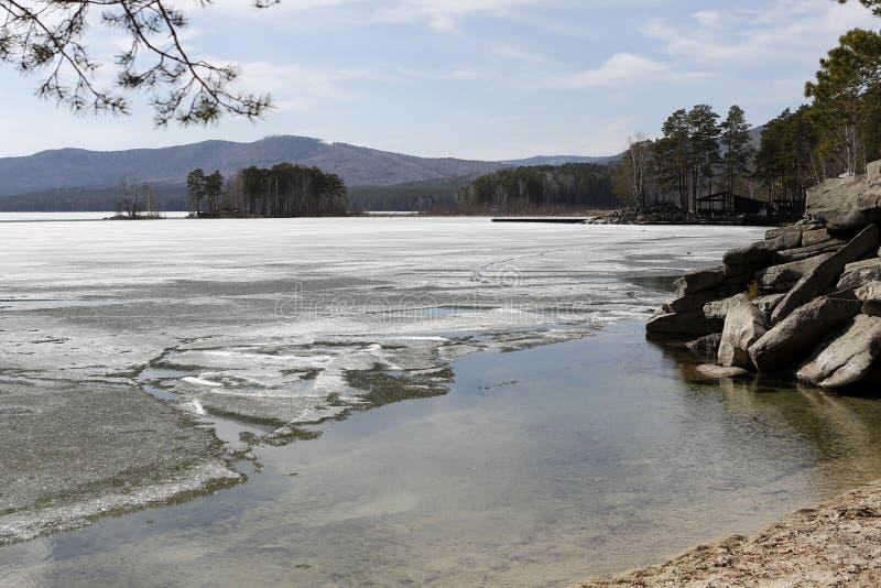 De lentelandschap op een meer met kusten royalty-vrije stock afbeelding
