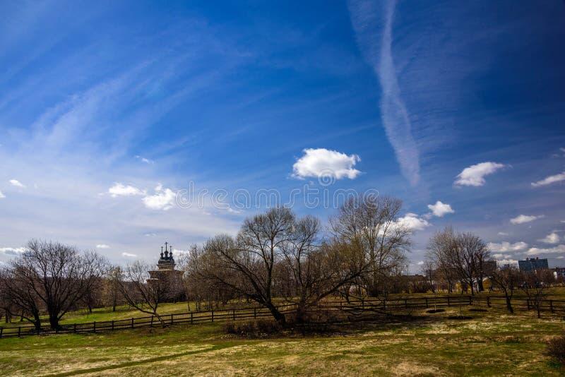 De lentepark Kolomenskoye met silhouet van een houten Orthodoxe Kerk van St George Zegevierend op de achtergrond stock afbeelding