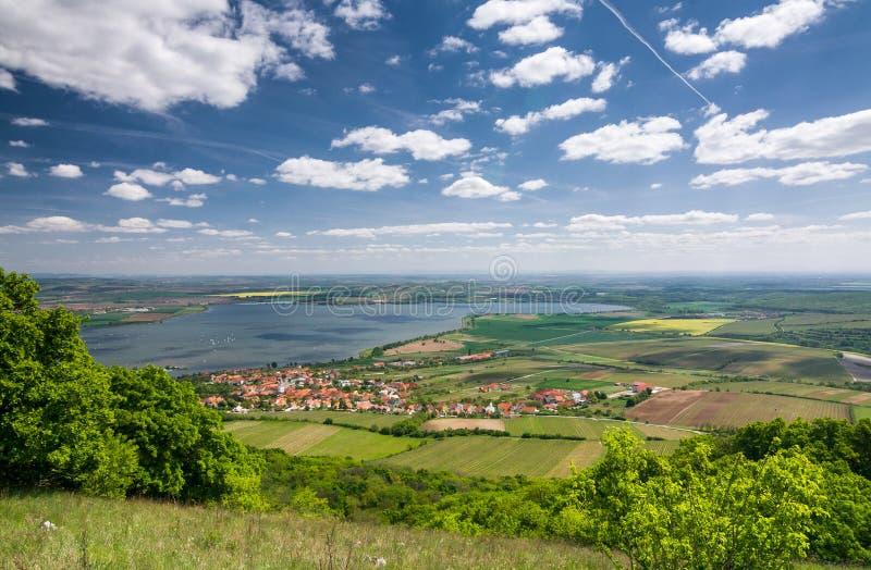 De lenteplatteland met dorp, meer, blauwe hemel en wolken royalty-vrije stock afbeeldingen