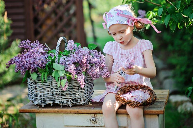 De lenteportret van aanbiddelijk kindmeisje die in roze kleding lilac kroon in zonnige tuin maken stock afbeeldingen