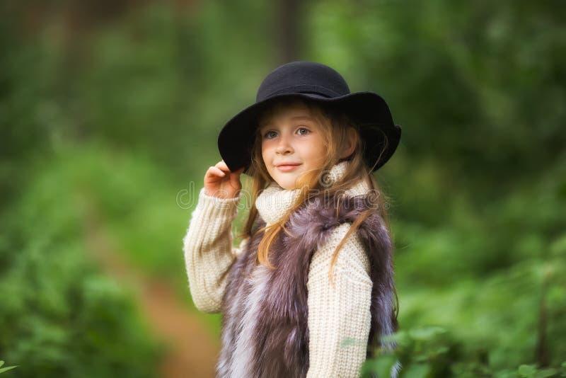 De lenteportret van een klein meisje Het zoete meisje met grote bruine ogen in een zwarte hoed en een bont bekleden stock foto