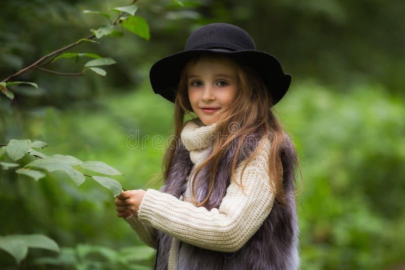 De lenteportret van een klein meisje Het zoete meisje met grote bruine ogen in een zwarte hoed en een bont bekleden royalty-vrije stock foto