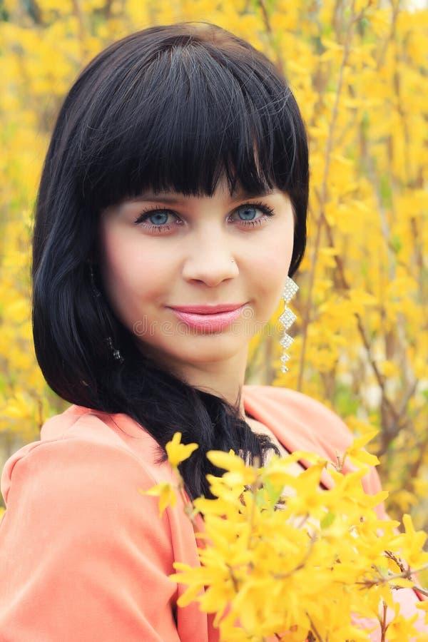 De lenteportret van een mooi brunette in gele bloemen stock afbeelding