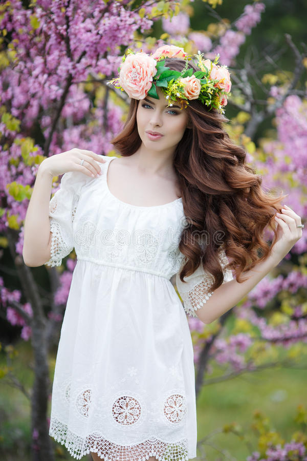 De lenteportret van een mooie vrouw in een kroon van bloemen stock afbeeldingen
