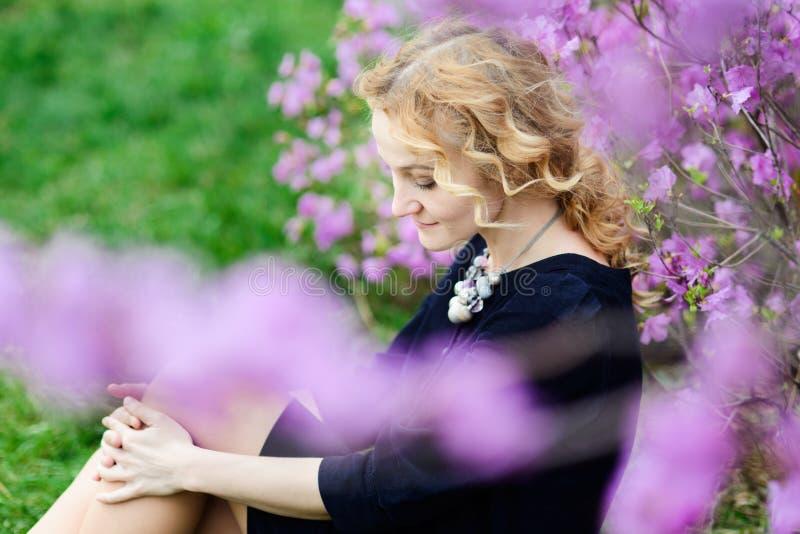 De lenteportret van nadenkende blondevrouw, violette bloemen stock foto's
