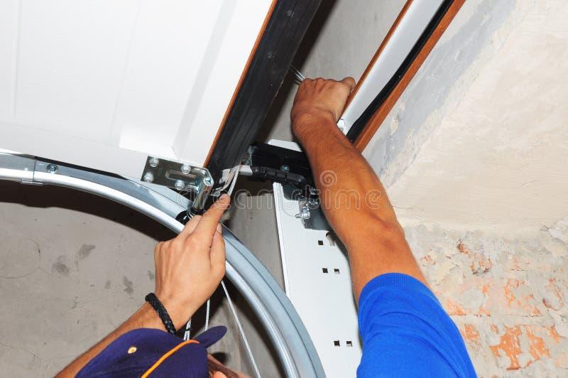 De Lentes van de de Garagedeur van de contractantreparatie De verbinding van de garagedeur, garagedeur springt, de vervanging van royalty-vrije stock afbeeldingen