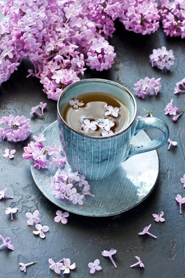 De lentesamenstelling met theekop en lilac bloemen stock foto's