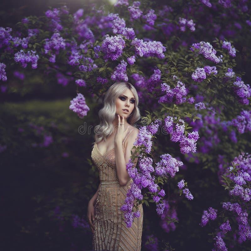 De lentestijl Mooi sensueel meisjesblonde in de lente Tot bloei komende de lentetuin Jong meisje in een gouden elegante kleding stock foto