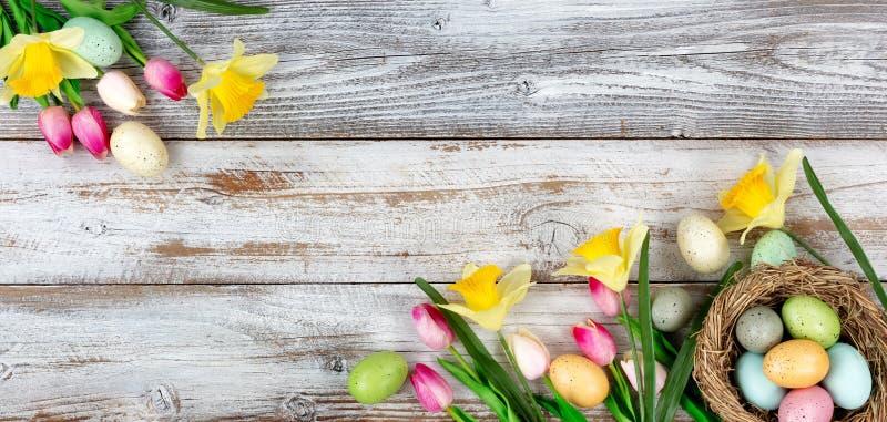 De lentetulpen en gele narcissen met kleurrijke eieren op rustieke houten raad voor Pasen-vakantieachtergrond stock fotografie