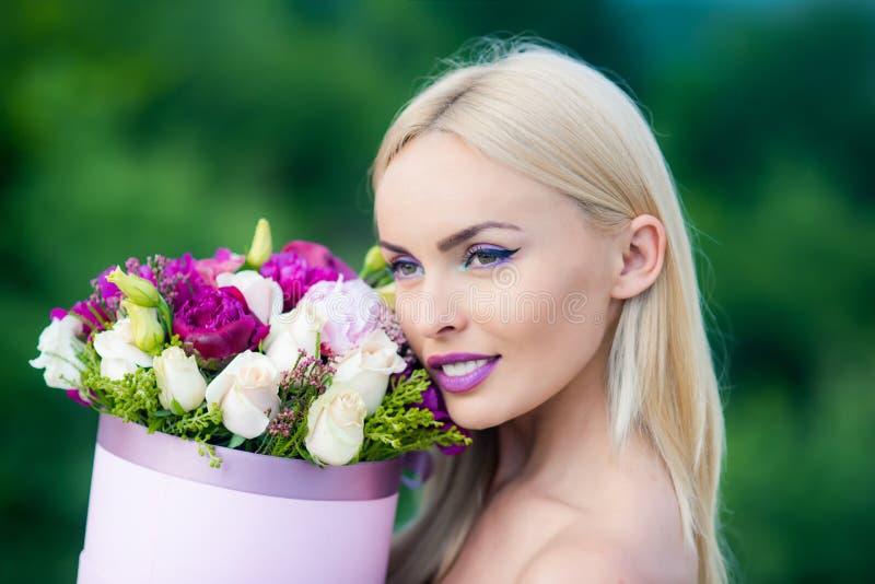 De lentevrouw met huidige bloemen De dag van vrouwen `s Schoonheidsdag in de lente Bloemendoos voor vrouw Valentine Beauty-blonde royalty-vrije stock foto