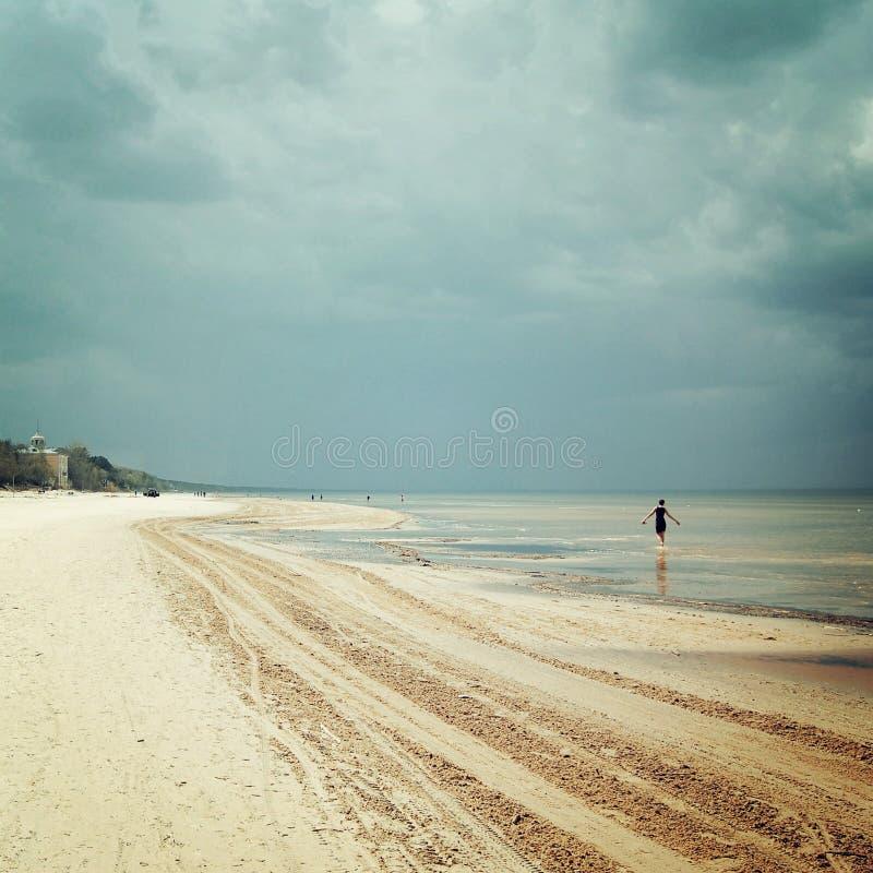 De lentezeegezicht met eenzaam meisjesfiguur - retro filter Zandige duinen en Oostzee - uitstekend effect royalty-vrije stock afbeelding