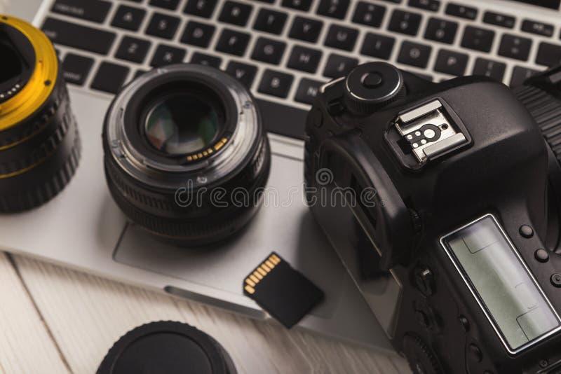 De lenzen van de fotocamera en geheugenkaart op computer stock afbeelding