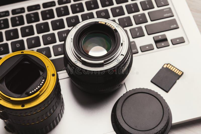 De lenzen van de fotocamera en geheugenkaart op computer royalty-vrije stock fotografie