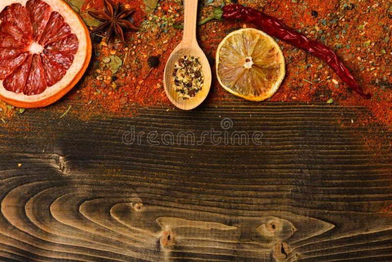 De lepel met keukenkruiden wordt gevuld, de Spaanse peper en de kurkuma leggen op houten achtergrond, exemplaarruimte die Speceri stock fotografie