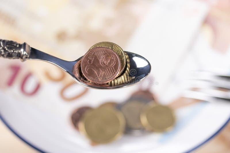 De lepel van het metaaldessert met een 2 cent muntstuk ge?tiketteerd SPANJE over een witte plaat met geld en een vork royalty-vrije stock afbeeldingen