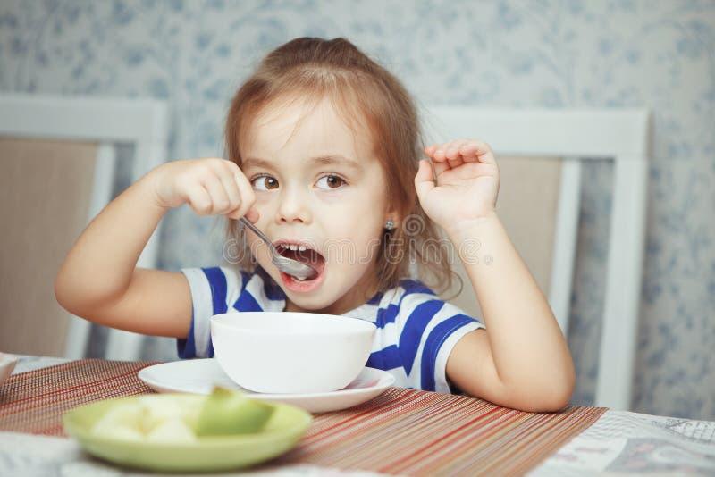 De lepel van de kindholding in haar hand die schotel eten royalty-vrije stock afbeeldingen