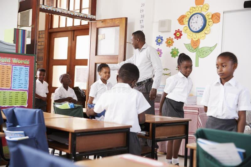 De leraar begroet jonge geitjes aankomend bij basisschoolklaslokaal royalty-vrije stock foto