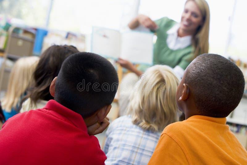 De leraar die van de kleuterschool aan kinderen leest royalty-vrije stock afbeeldingen