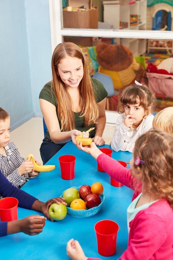 De leraar en de kinderen eten fruit in het opvangcentrum royalty-vrije stock foto