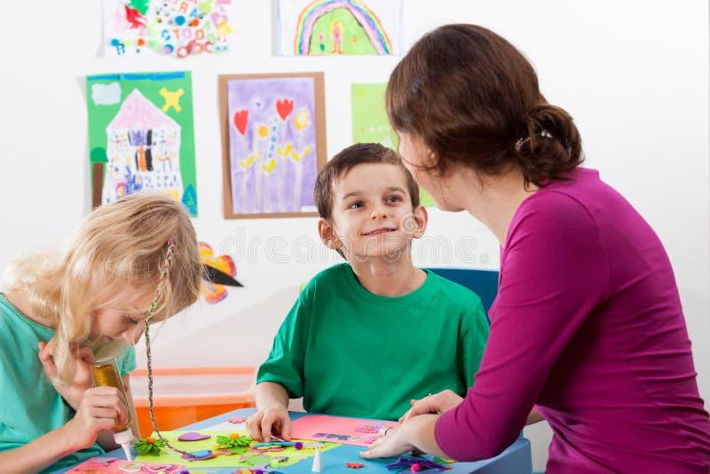 De leraar helpt kinderen stock foto's