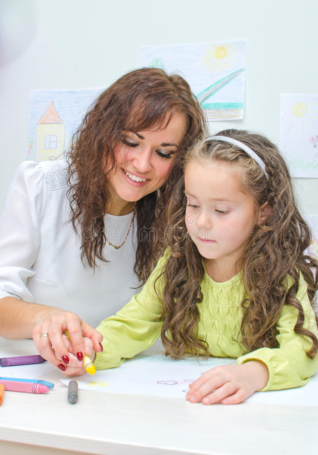 De leraar helpt meisje stock afbeelding