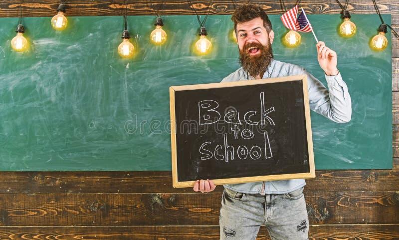 De leraar houdt bord met geschreven uitdrukking terug naar school en vlag van de V.S. Amerikaans schoolconcept Mens met baard  royalty-vrije stock afbeeldingen