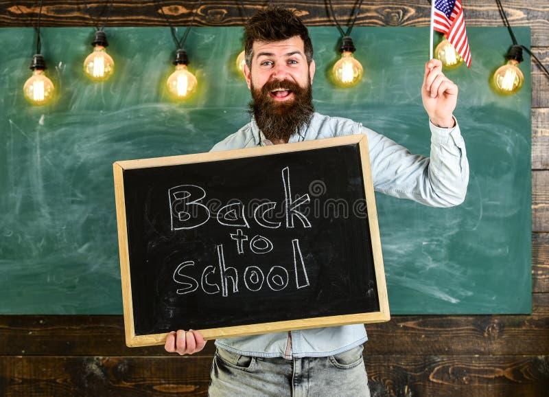 De leraar houdt bord met geschreven uitdrukking terug naar school en vlag van de V.S. De mens met baard op het glimlachen gezicht stock fotografie