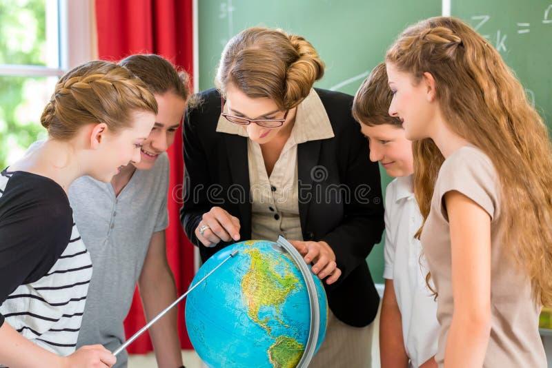 De leraar leidt studenten op die aardrijkskundelessen in school hebben stock fotografie