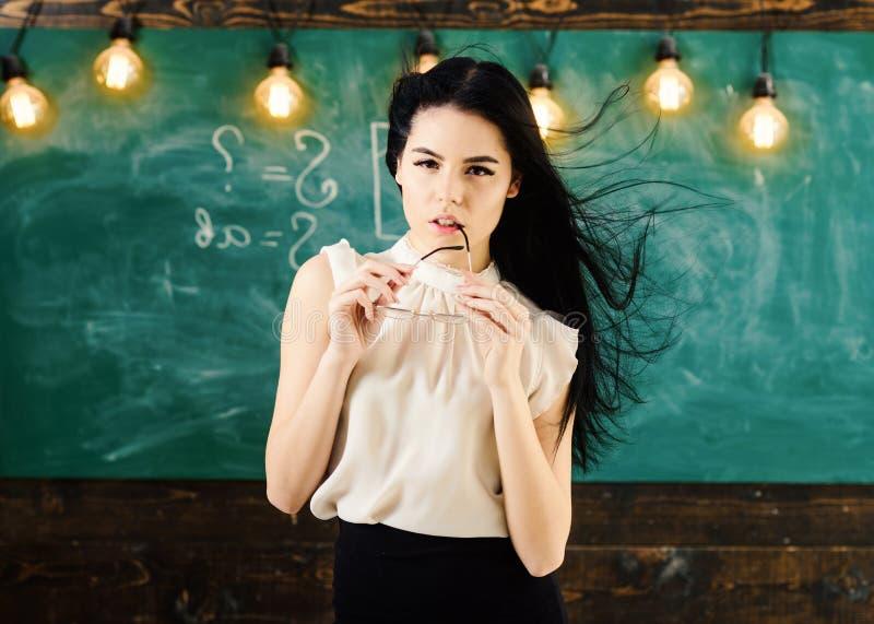 De leraar met glazen en golvend haar kijkt sexy Vrouw met lang haar in witte blousetribunes in klaslokaal Strikte dame royalty-vrije stock fotografie