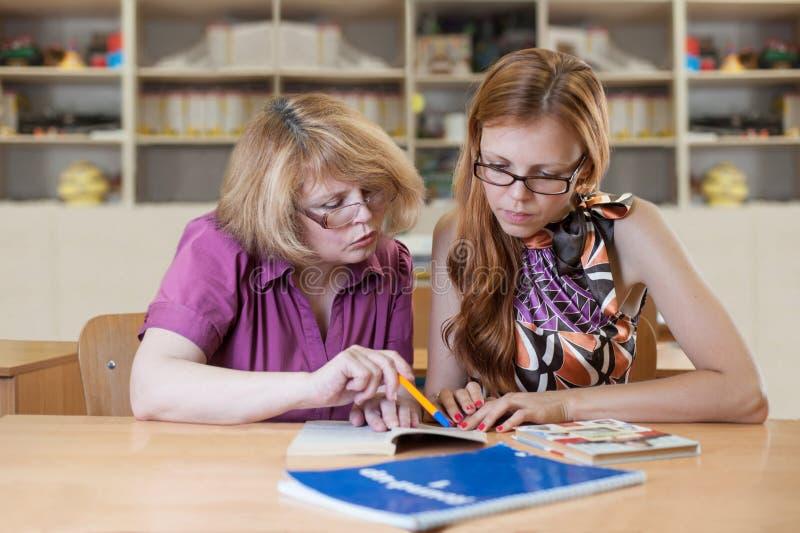 De leraar onderwijst een student bij een lijst in het klaslokaal stock afbeelding