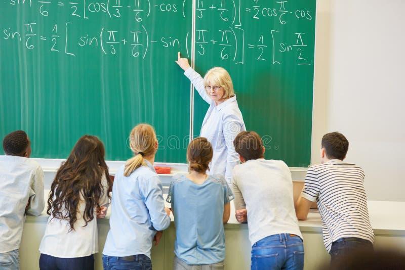 De leraar in wiskundeklasse verklaart formule stock afbeeldingen