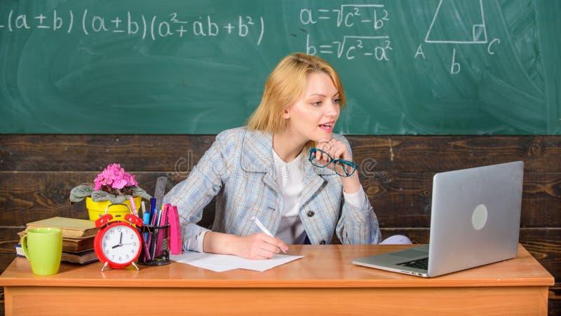 De leraarsvrouw zit laptop van het lijstwerk surfend Internet-bordachtergrond Organiseer klasse en maak leren gemakkelijk stock foto's
