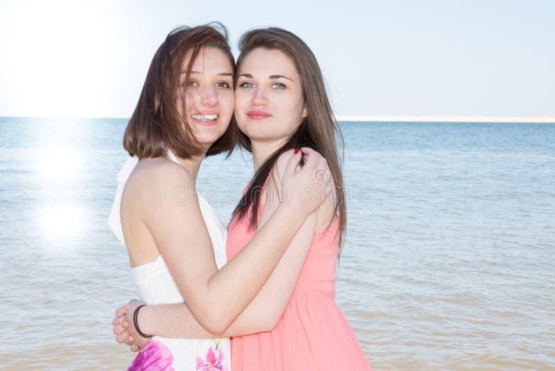 De lesbienne lgbt koppelt het bekijken de zon terwijl het koesteren van elkaar op strand stock foto's
