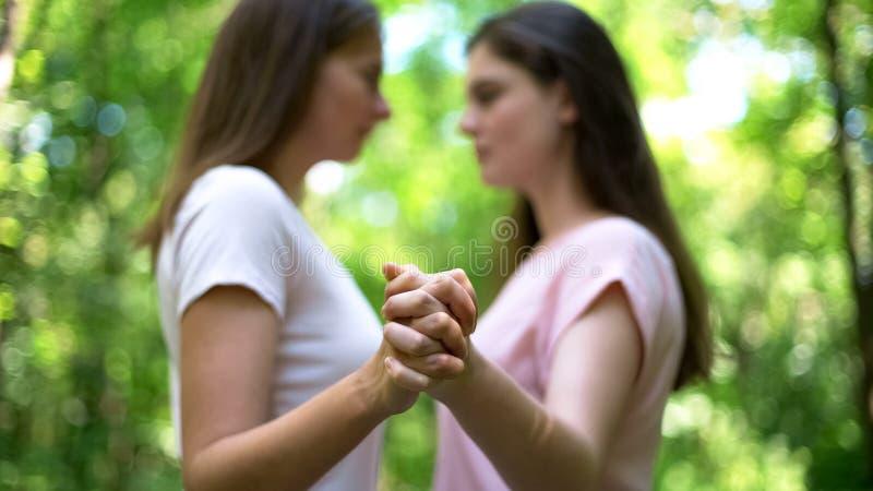 De lesbiennes die handen houden, voelen aantrekkelijkheid aan elkaar, vertrouwende zelfde-geslachtsliefde royalty-vrije stock afbeelding