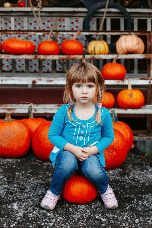 de leuke aanbiddelijke witte Kaukasische roodharige zitting van het meisjekind op grote pompoen op landbouwbedrijf royalty-vrije stock foto's
