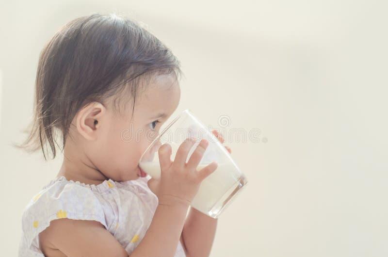 De leuke Aziatische consumptiemelk van het peutermeisje van groot glas op witte bedelaars stock foto