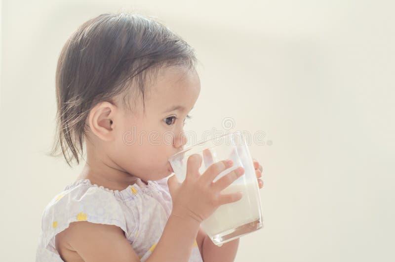 De leuke Aziatische consumptiemelk van het peutermeisje van groot glas op witte bedelaars stock afbeeldingen