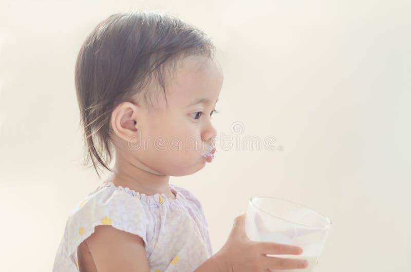 De leuke Aziatische consumptiemelk van het peutermeisje van groot glas op witte bedelaars stock foto's