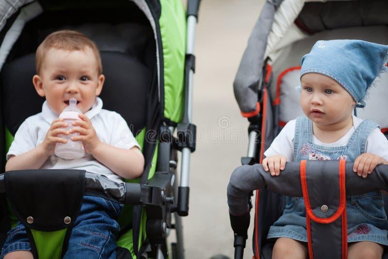 De leuke baby drinkt sapzitting in kinderwagen royalty-vrije stock foto