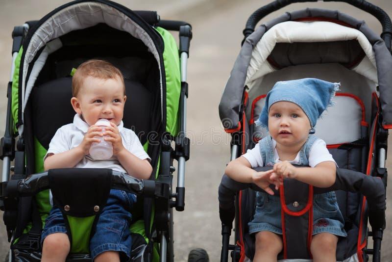 De leuke baby drinkt sapzitting in kinderwagen stock foto's