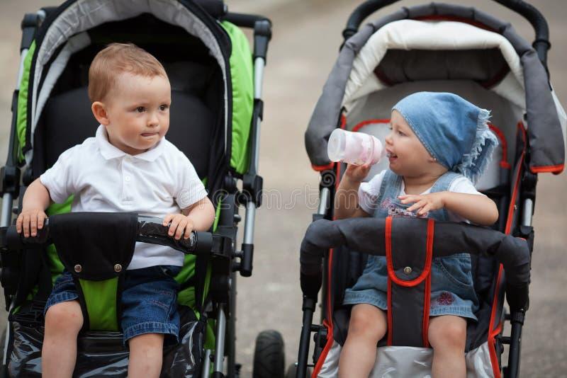 De leuke baby drinkt sapzitting in kinderwagen stock foto