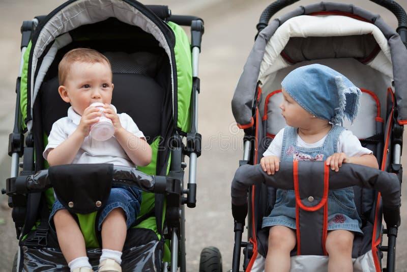 De leuke baby drinkt sapzitting in kinderwagen stock afbeeldingen